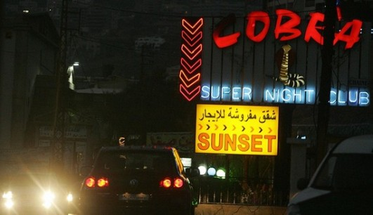 """Jounieh, LEBANON: TO GO WITH AFP STORY """"AFPLIFESTYLE-MIDEAST-CONFLICT-LEBANON"""" Cars drive past a cabaret nestled on a hill on the tip of the Bay of Jounieh, in the Christian heartland north of Beirut, late 03 August 2006. From the glamour of the Casino du Liban for the high society to downright seedy bars for the low-life, Lebanon even in wartime caters for all tastes. AFP PHOTO/Patrick BAZ (Photo credit should read PATRICK BAZ/AFP/Getty Images)"""