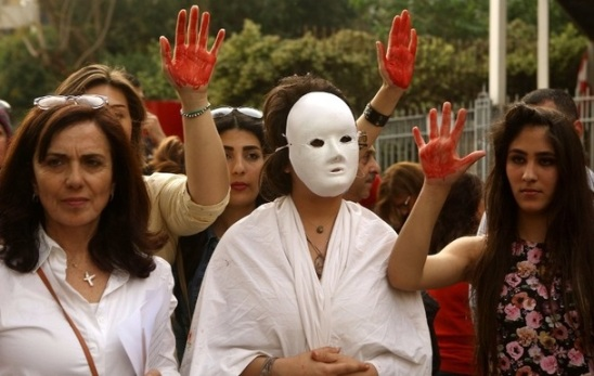Lebanese women flash the palm of their hands colored in red as they demonstrate against prostitution, sex slavery and violence against women in front of the Justice Palace in the capital Beirut on April 8, 2016. / AFP PHOTO / PATRICK BAZ