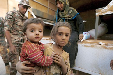 Syrian refugee children covered with dust arrive Sept. 10 at the Jordanian border with Syria and Iraq, near the town of Ruwaished, which is close to Amman, Jordan. (CNS photo/Muhammad Hamed, Reuters) See SYRIAN-REFUGEES-KURTZ Sept. 11, 2015.